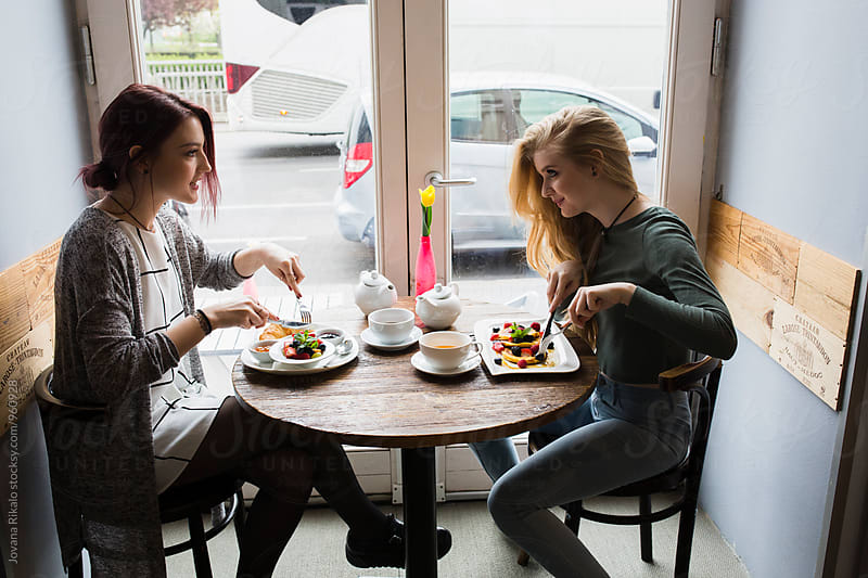 Two female friends having breakfast by Jovana Rikalo for Stocksy United