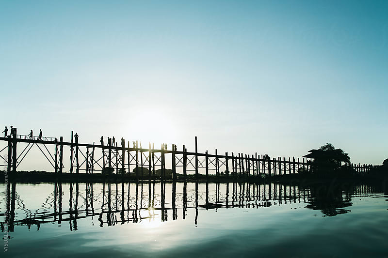 Silhouette of People Walking on Long Wooden Bridge at Sunset Time by VISUALSPECTRUM for Stocksy United