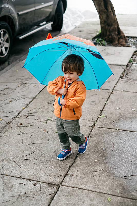 Young boy walking down the street holding an umbrella before the rain storm. by Lucas Saugen for Stocksy United