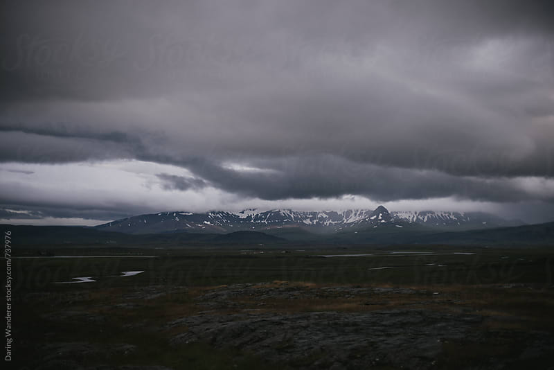 Dark and moody clouds over mountain landscape in Iceland by Daring Wanderer for Stocksy United