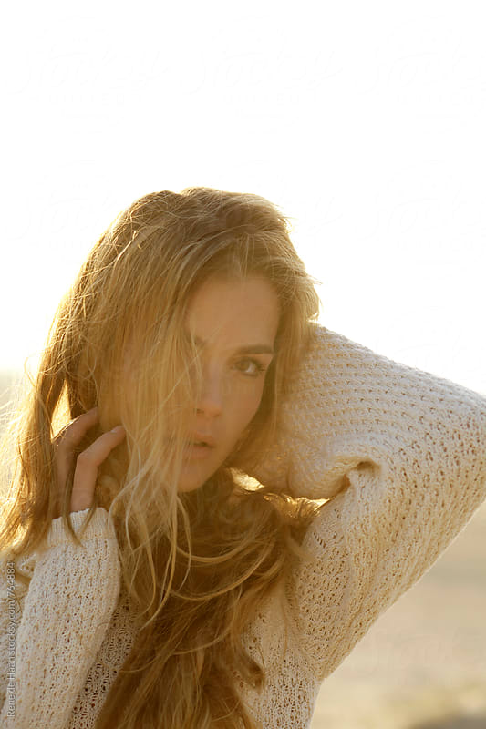 young woman with blonde hair, in nature, at sunset by Rene de Haan for Stocksy United