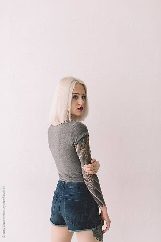 portrait of young blond woman with tattoos on the white background by Alexey Kuzma for Stocksy United