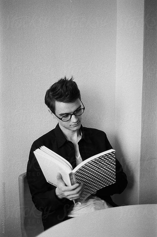 A black and white film portrait of a young beautiful man reading a book by Anna Malgina for Stocksy United