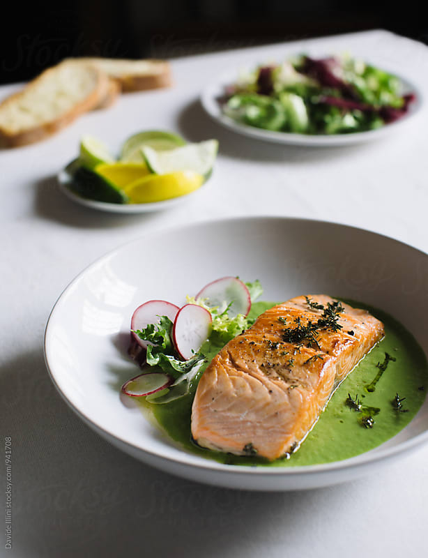 Salmon fillet with asparagus sauce and mixed salad by Davide Illini for Stocksy United