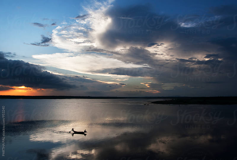 Two fishermen with floating vessel in a lake at evening time by PARTHA PAL for Stocksy United