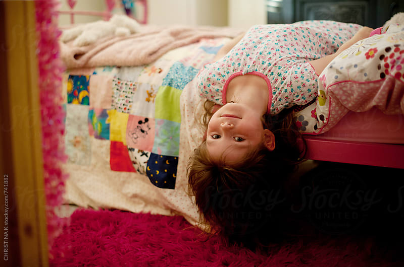 Little girl hanging upside down off the side of her bed by CHRISTINA K for Stocksy United