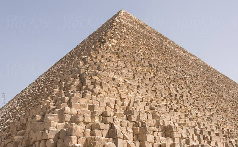 Low wide angle shot of pyramid against a blue sky. by Mike Marlowe for Stocksy United