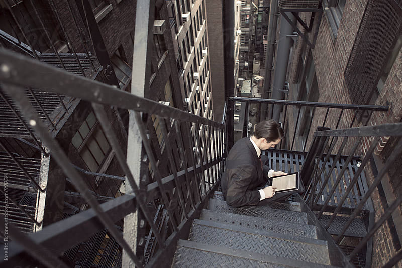 Retro Look Man in Suit Using Tablet in New York Old Building Fire Escape Stairs by Joselito Briones for Stocksy United