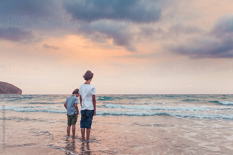 Two boys standing in the ocean during sunset in the summer by Cindy Prins for Stocksy United