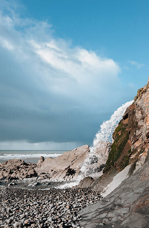 Waterfall flowing from a cliff onto the beach by Suzi Marshall for Stocksy United