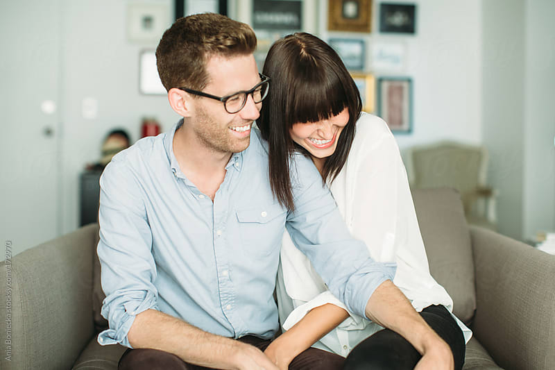 Happy couple laughing together at home by Ania Boniecka for Stocksy United