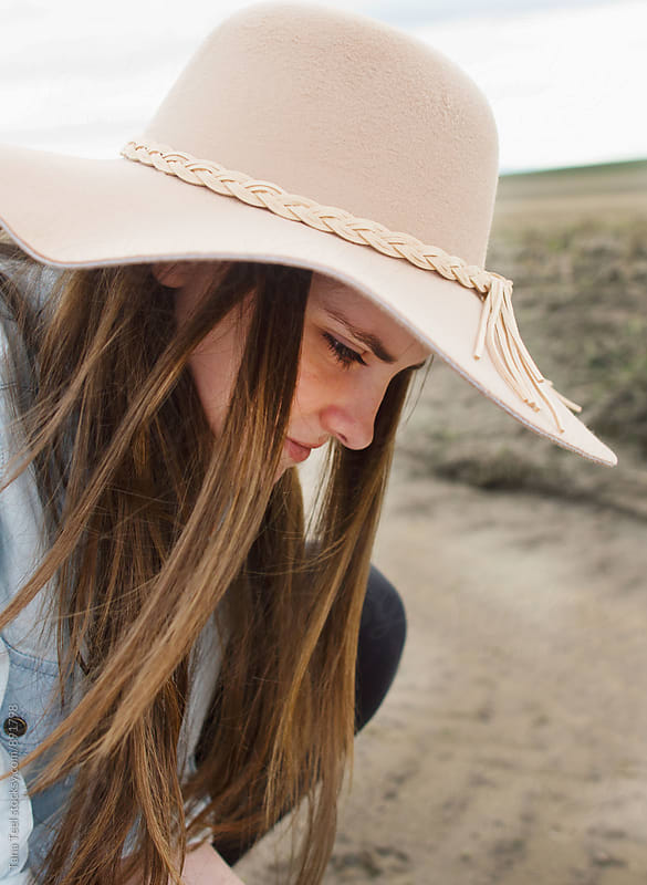 young woman wearing hat bends down  by Tana Teel for Stocksy United