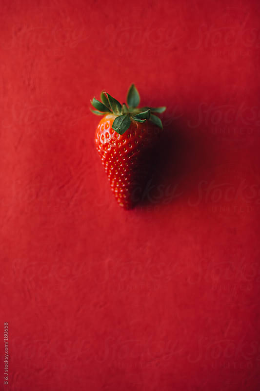 Strawberry on a Red Background by B & J for Stocksy United