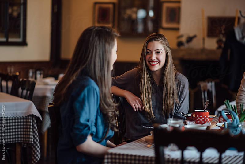 Friends having a conversation in restaurant by Boris Jovanovic for Stocksy United