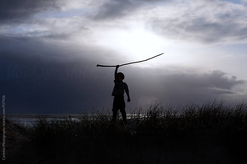 Silhouette of boy raising stick above his head at sunset by Carleton Photography for Stocksy United