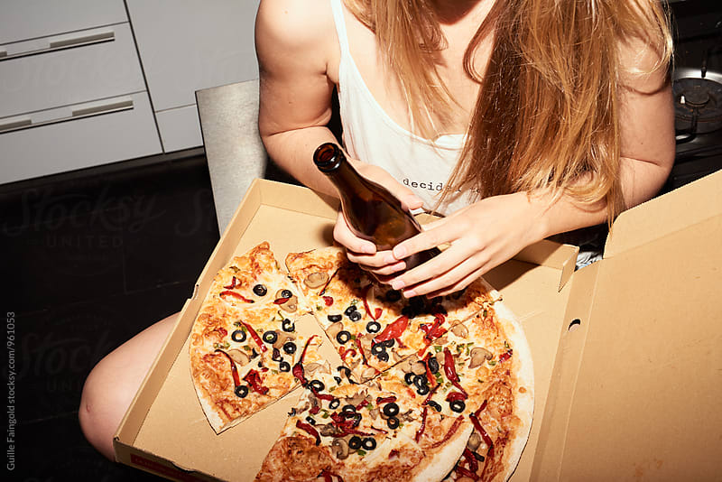 Close-up of woman with box of pizza and beer by Guille Faingold for Stocksy United