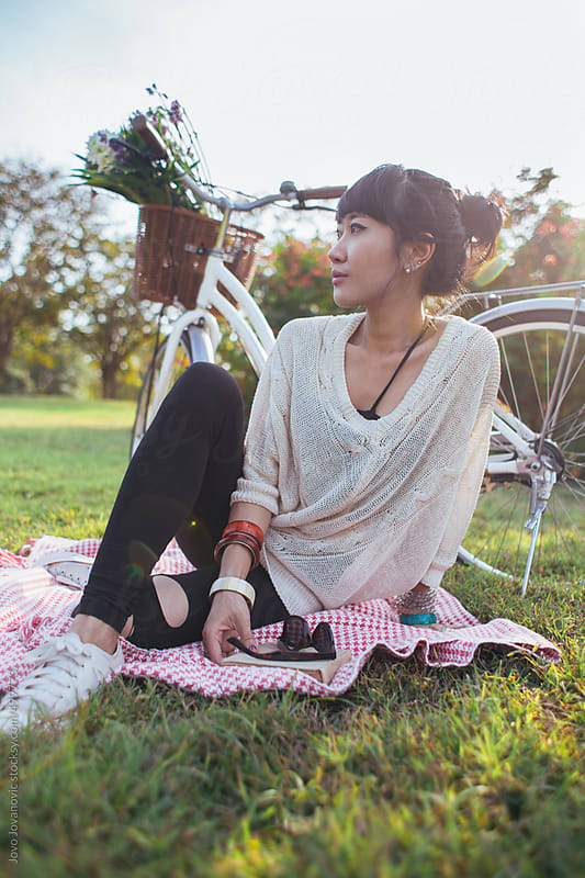 Spring time - woman sitting on a picnic rug and thinking by Jovo Jovanovic for Stocksy United