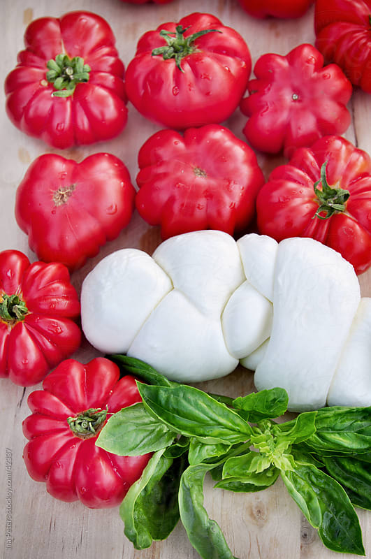 Food: Bulls heart tomatos with mozzarella cheese and basil by Ina Peters for Stocksy United