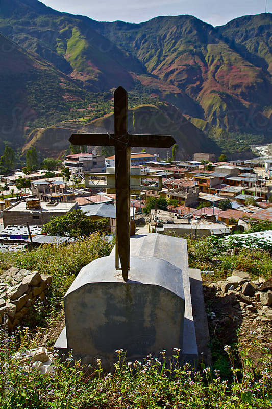 A grave with a cross at a cemetery on a hill over looking the hillside town of Saint Teresa, Peru  by Jaydene Chapman for Stocksy United