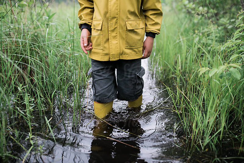 little boy on walk in a flooded path by Léa Jones for Stocksy United