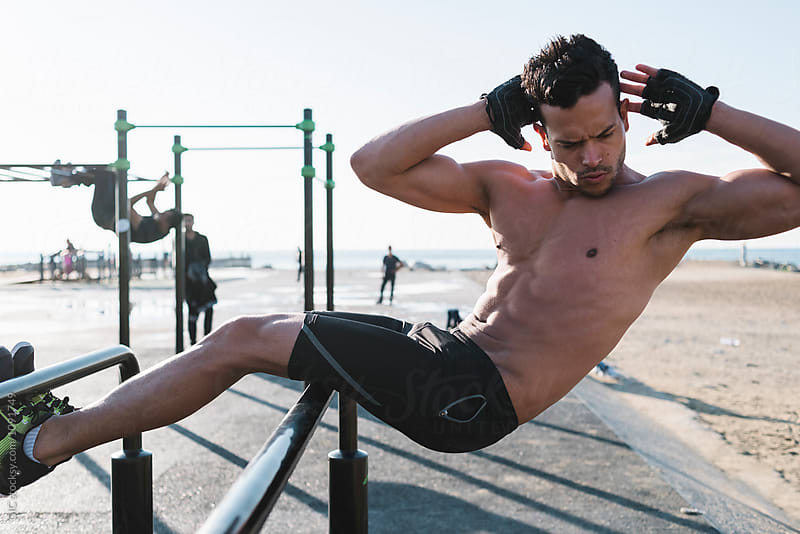 Young man doing abdominal exercises outdoors by Simone Becchetti for Stocksy United