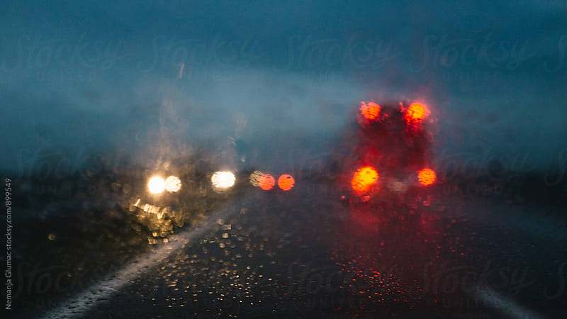 Blurred Headlights in Distance on a Highway on a Rainy Night by Nemanja Glumac for Stocksy United