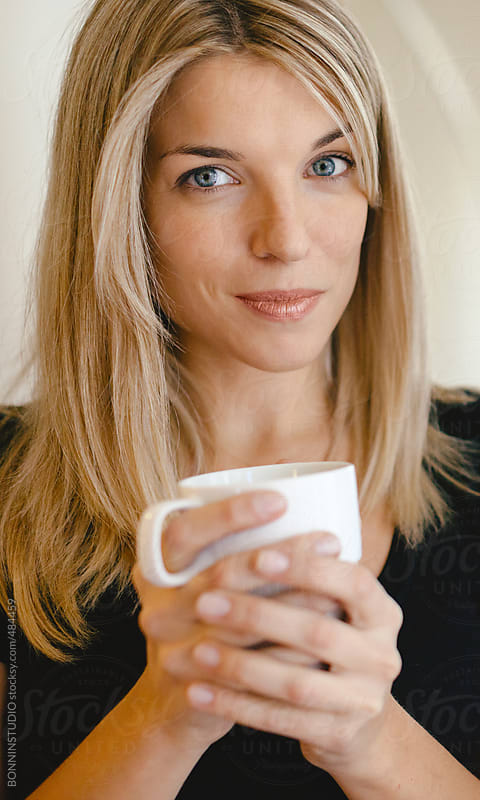 Portrait of beautiful blonde woman drinking coffee at home.  by BONNINSTUDIO for Stocksy United