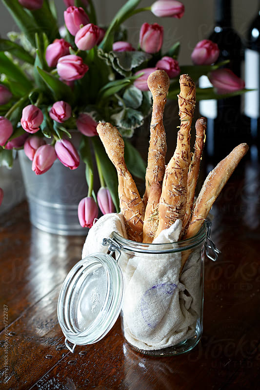Handmade breadsticks in a jar on a dark table with tulips and wine by Sherry Heck for Stocksy United