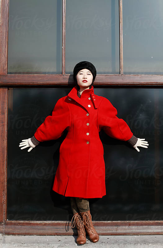 young chinese woman in red coat in front of window by Rene de Haan for Stocksy United
