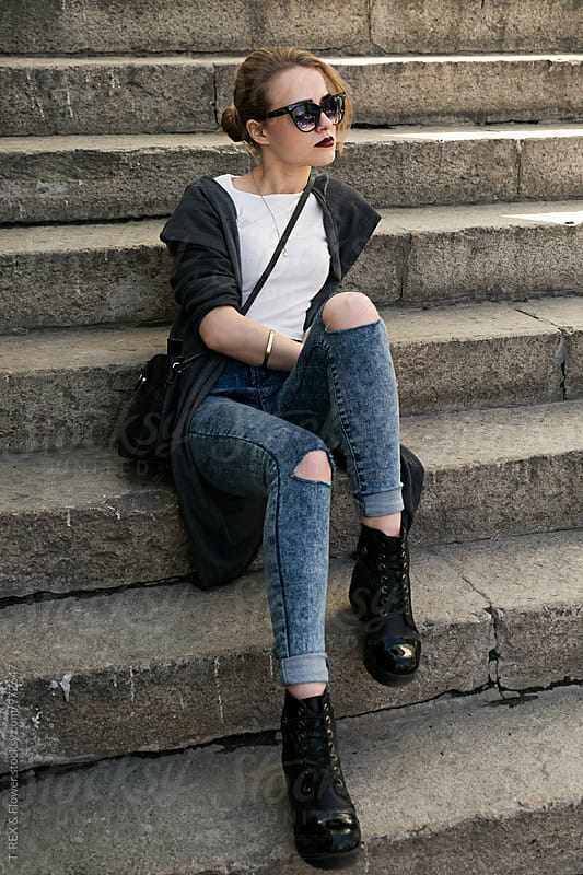 Portrait of young stylish woman on stairs by Danil Nevsky for Stocksy United