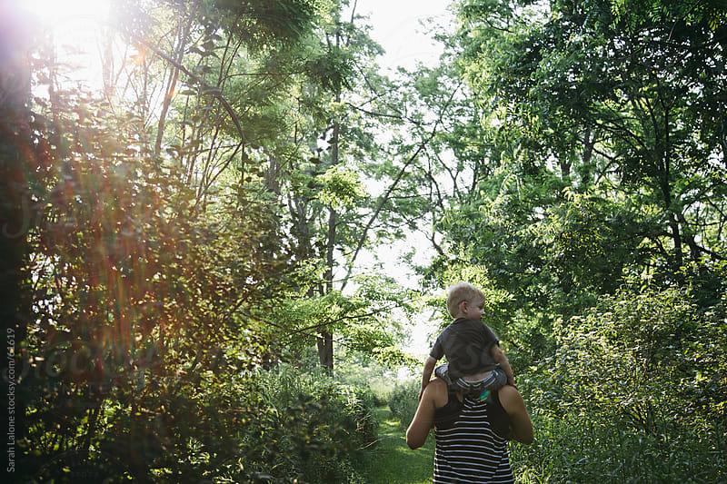 A woman walking in the woods with a little boy on her shoulders. by Sarah Lalone for Stocksy United