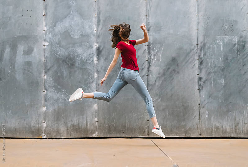Woman jumping against a wall by WAVE for Stocksy United