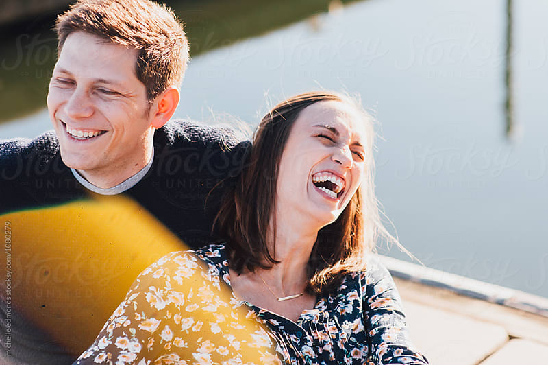 Couple Laughing Together on a Boat Dock by michelle edmonds for Stocksy United