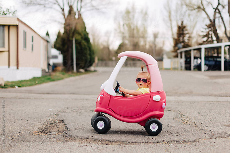 Toddler girl with pink sunglasses in pink toy car by Jessica Byrum for Stocksy United