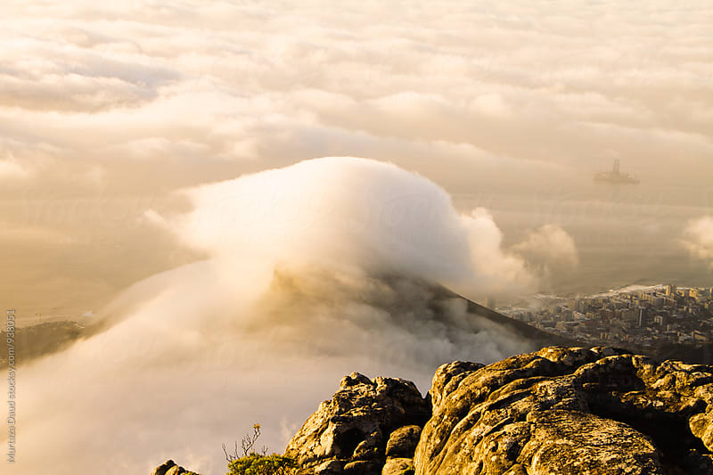 Clouds hurling over a mountain peak in Cape Town by Murtaza Daud for Stocksy United