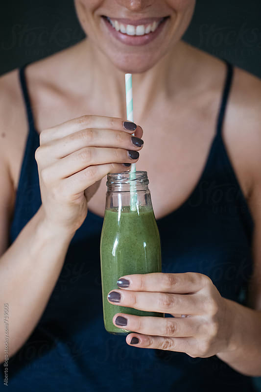 Smiling woman holding green smoothie by Alberto Bogo for Stocksy United