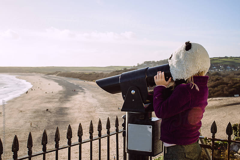 A little girl in a panda hat looking through a telescope overlooking a beach. by Helen Rushbrook for Stocksy United