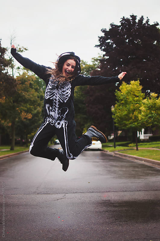 A young woman wearing a skeleton onesie jumping in the air by Chelsea Victoria for Stocksy United