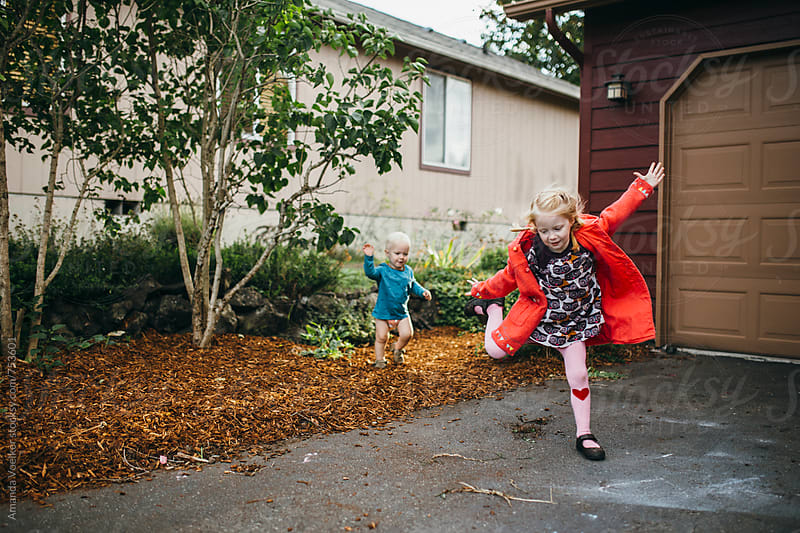 Young girl dancing in her driveway while her little brother watches by Amanda Voelker for Stocksy United