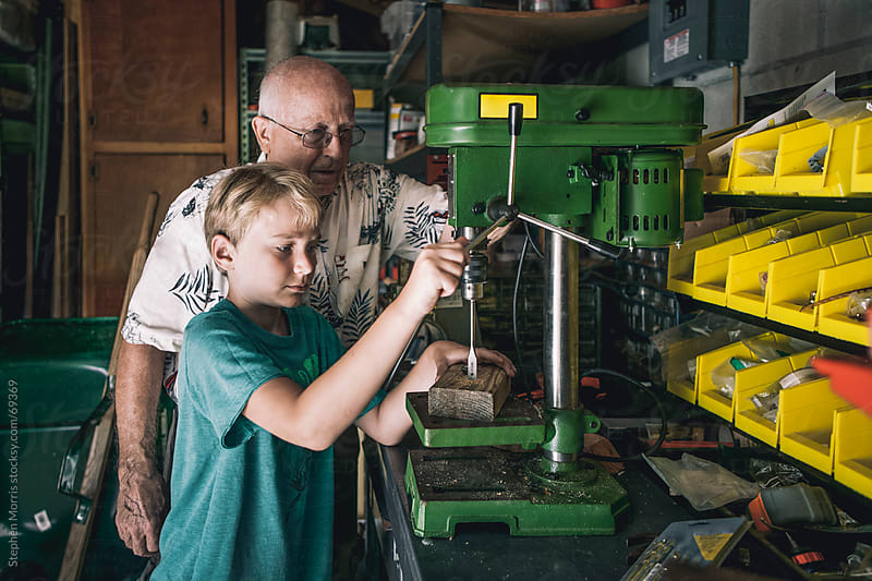 Grandfather teaching Grandson in Workshop by Stephen Morris for Stocksy United