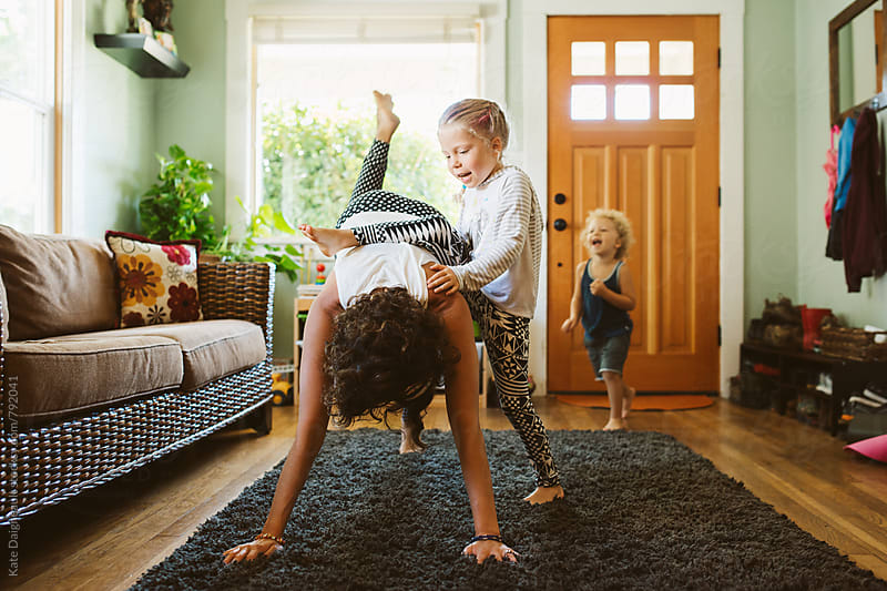 Young mom trying to do yoga in living room with her two children by Kate Daigneault for Stocksy United