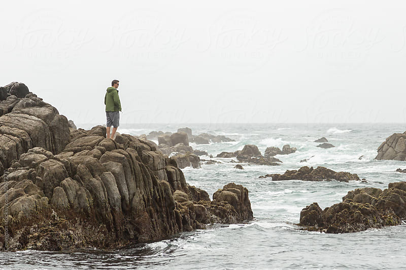 Man on jagged rocks looking out over the Pacific Ocean  by Amy Covington for Stocksy United