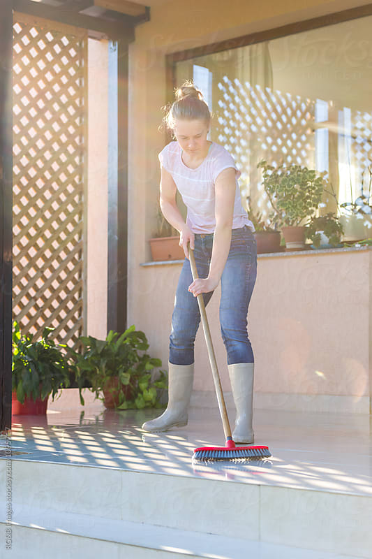 Young woman washing the porch floors at home by RG&B Images for Stocksy United
