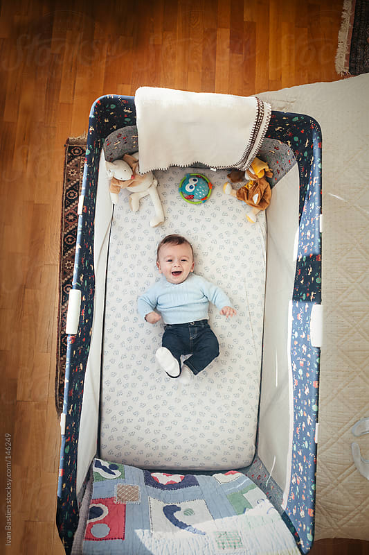 Happy baby boy laughing in a bed by Ivan Bastien for Stocksy United