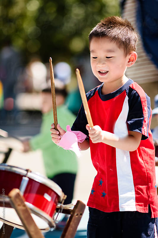 Child holding drumstick and playing drum in sunlight by Lawren Lu for Stocksy United