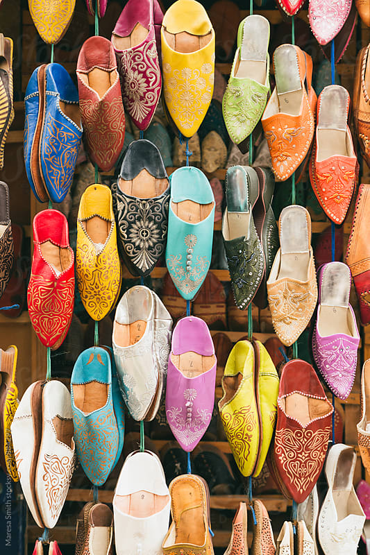 Colourful Moroccan slippers hanging at a market stall by Maresa Smith for Stocksy United