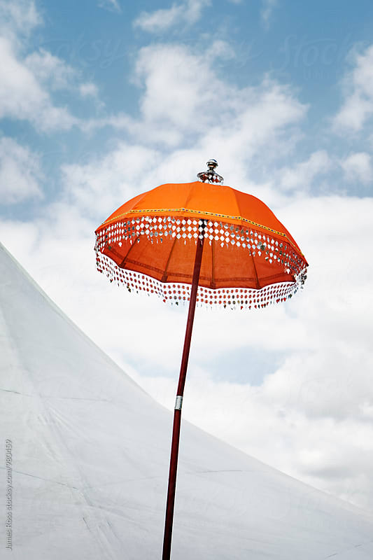 Parasol by a tent with blue skies by James Ross for Stocksy United