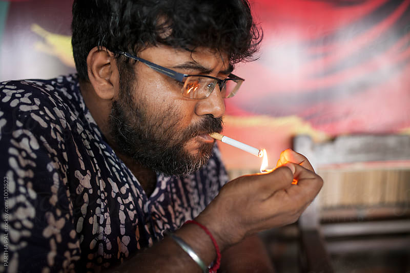 A man lighting cigeratte with match stick by PARTHA PAL for Stocksy United