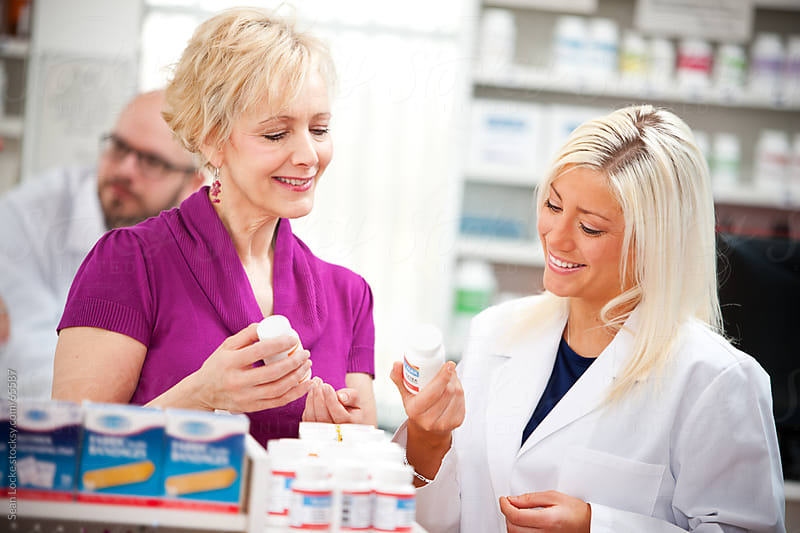 Pharmacy: Customer and Pharmacist Work Together to Find Right Me by Sean Locke for Stocksy United