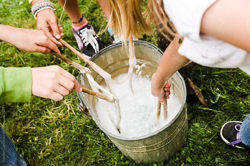 Kids dipping string and sticks into a bucket of soap for old school bubbles by Carolyn Lagattuta for Stocksy United